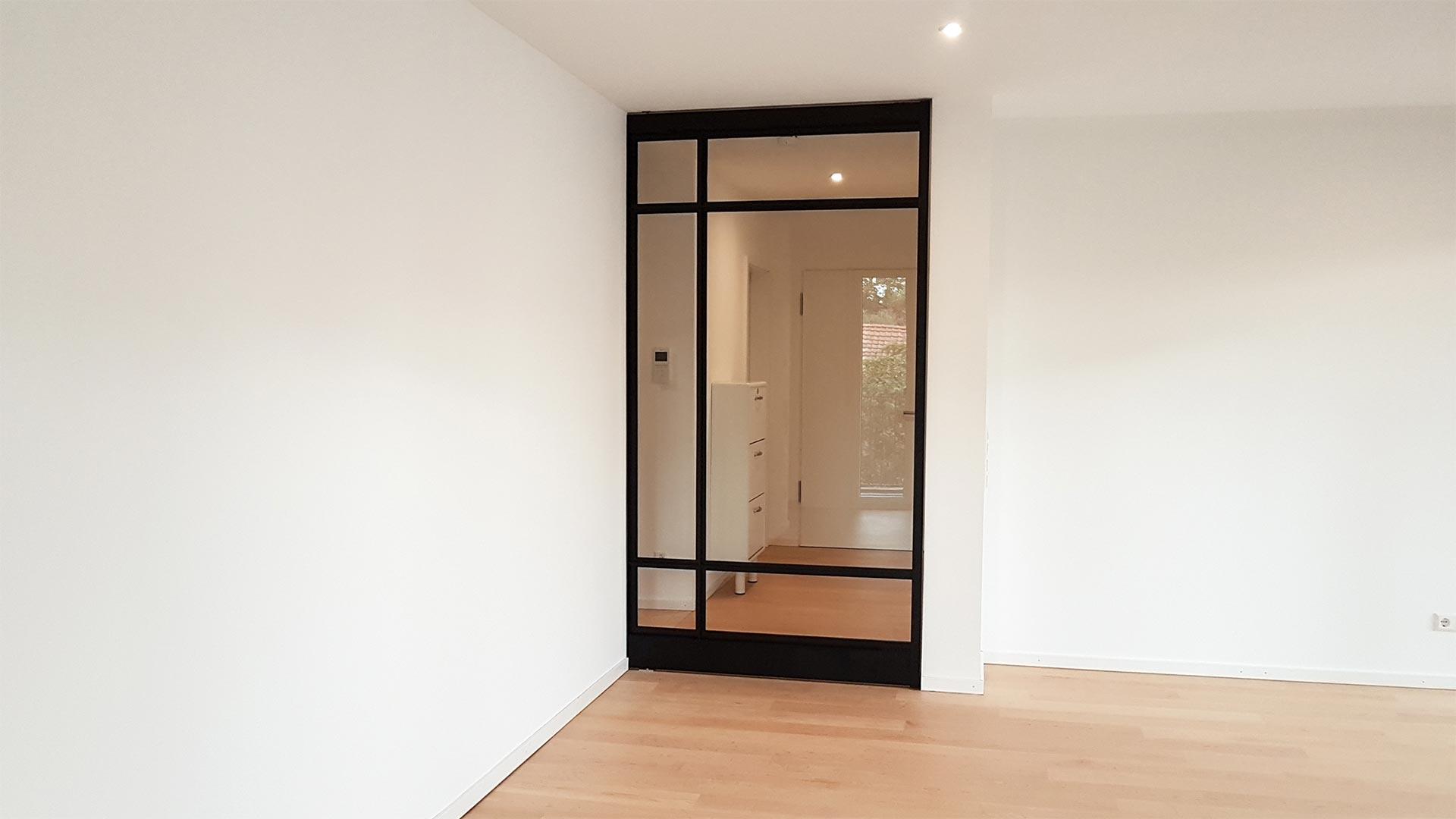 Pivot-Tür mit Glasleisten aus pulverbeschichtetem Stahl geschlossen.